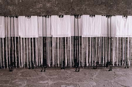 Helene Aylon   The Partition is in Place, But The Service Can't Begin , 2001   metal racks, thread, ritual male garb (Tsitsit), 21' W x 2' D x 6' H